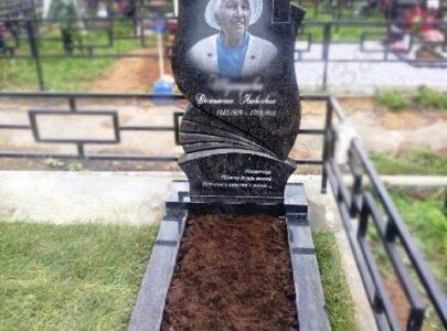 Памятник з кольоровою фотографією на кладовищі